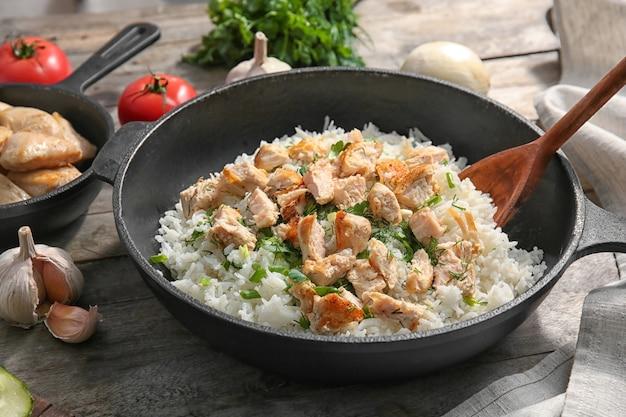 Koekenpan met kip en rijst op keukentafel