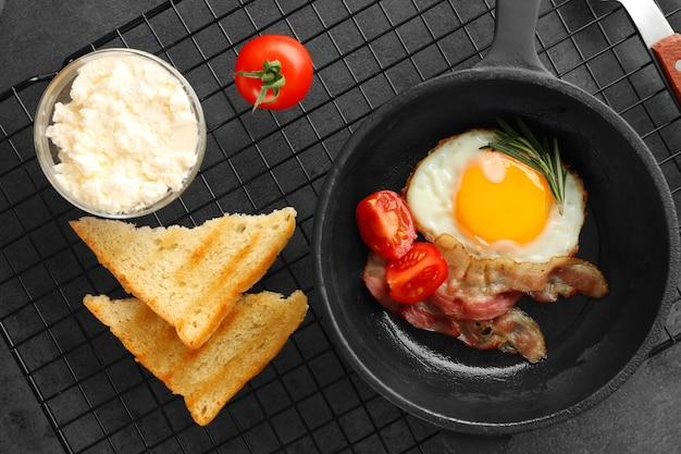 Koekenpan met lekker ei en spek voor het ontbijt op tafel