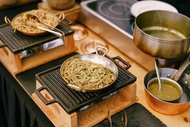 Koekenpannen met spaghetti op een gietijzeren fornuis in de keuken