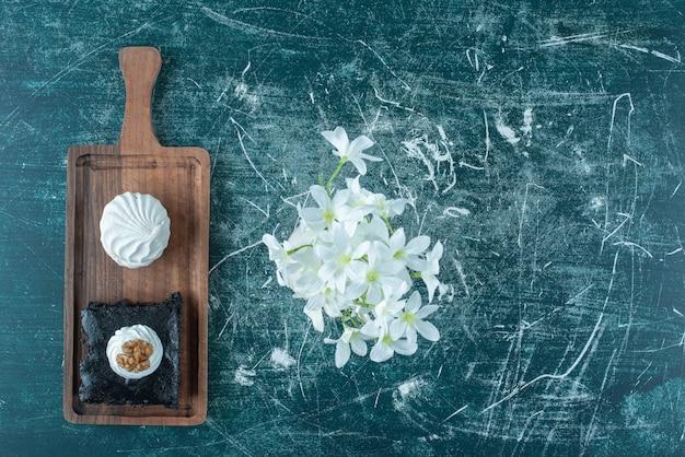 Koekje en een plakje cake op een klein dienblad naast een vaas met witte lelies op blauw.