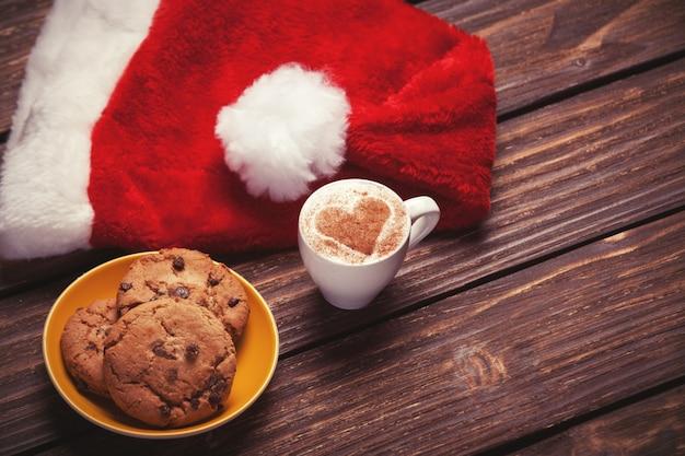Koekje en kopje koffie met kerstmuts op houten tafel.
