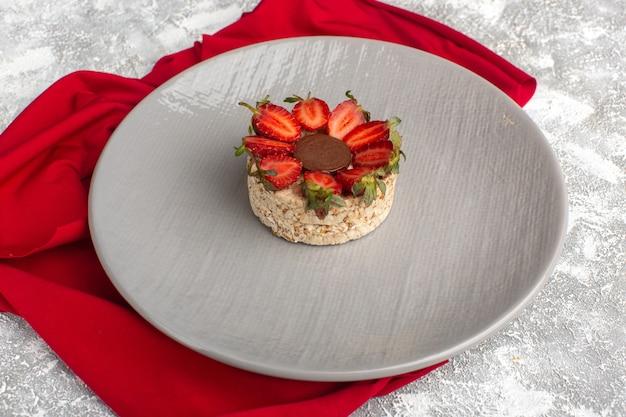 Koekje met aardbeien en ronde chocolade binnen paarse plaat