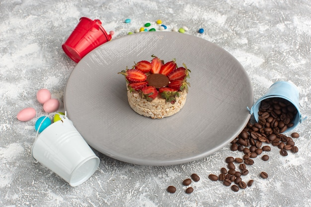 Koekje met aardbeien en ronde chocolade in paarse plaat, samen met koffiezaden en snoepjes