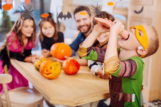 Koekje proberen. schooljongen die een geel oogmasker draagt voor halloween en een lief en eng handkoekje probeert
