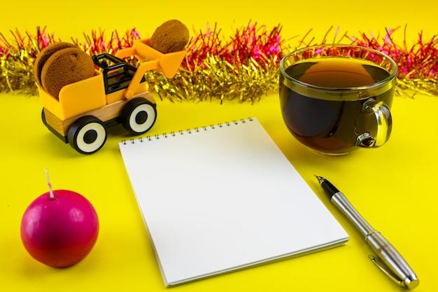 Koekjes, een kaars, een grote kop thee, een notitieboekje en een pen op een oudejaarsavondachtergrond.