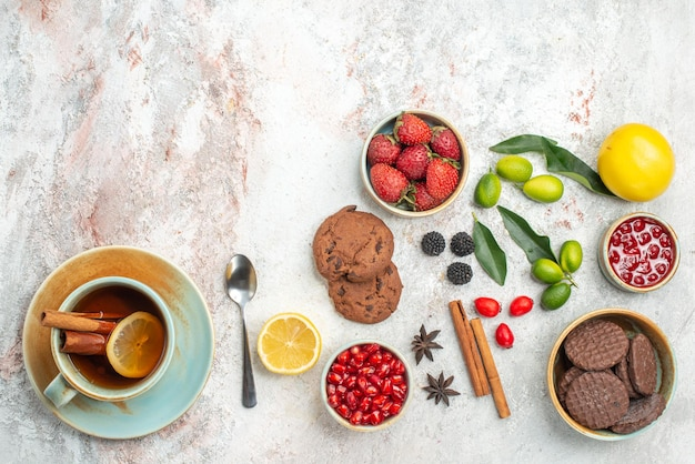 Koekjes en aardbeien granaatappel steranijs koekjes aardbeien een kopje thee citrusvruchten kaneelstokjes vork op tafel