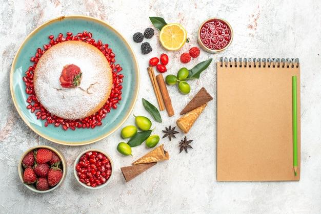 Koekjes en cake een taart bessen jam citrusvruchten kaneel notitieboekje potlood