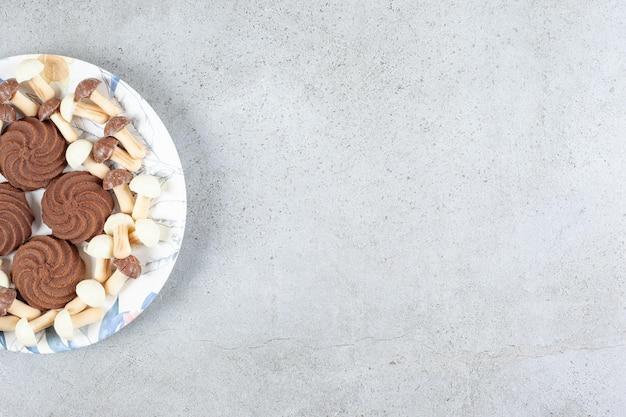 Koekjes en chocoladepaddestoelen op een plaat op marmeren oppervlakte