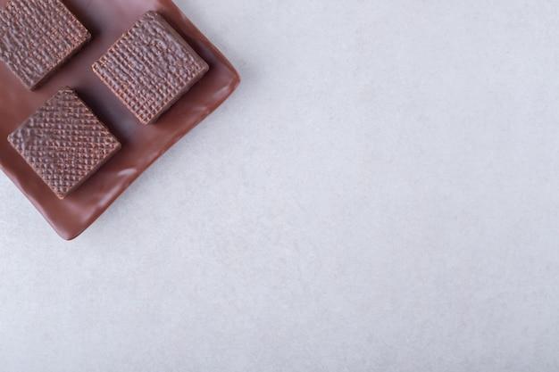 Koekjes en chocoladewafels op houten plaat op marmeren tafel.