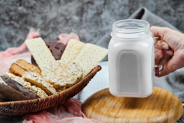 Koekjes- en cracker-variëteiten met een pot melk.