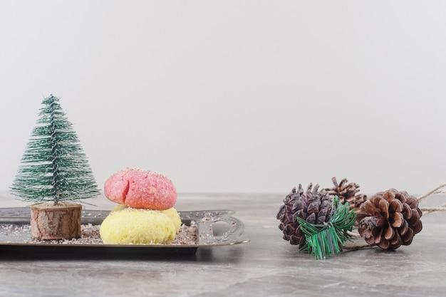 Koekjes en een boomfiguur op een dienblad naast dennenappels op marmer