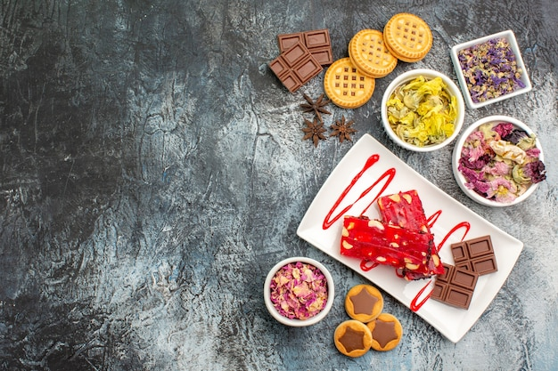 Koekjes en een bord chocolade met kommen droge bloemen op de rechterzijde van grijs