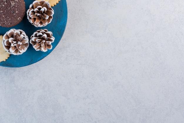 Koekjes en een chocoladetaart op een blauw bord met dennenappels op marmeren tafel.