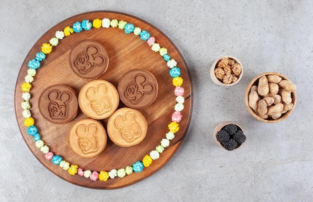 Koekjes en een cirkel van snoepjes op een houten bord naast kommen van pinda's en moerbeien op marmeren achtergrond. hoge kwaliteit foto