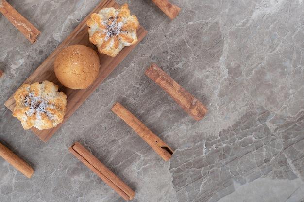 Koekjes en een cupcake op een kleine serveerplank, omringd met kaneelstokjes op marmeren ondergrond