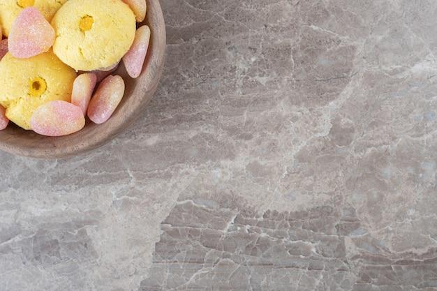 Koekjes en gelei-snoepjes gebundeld in een kleine kom op een marmeren oppervlak