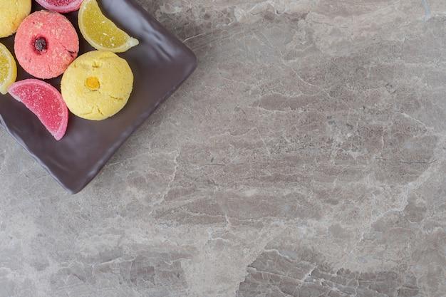 Koekjes en gelei-snoepjes gebundeld op een schaal op een marmeren oppervlak