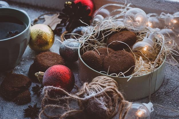 Koekjes en hete thee koffie in een beker nieuwjaars donkere achtergrond gezellige kerstsfeer