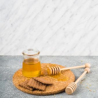 Koekjes en honingspot met houten dipper op corkonderlegger voor glazen