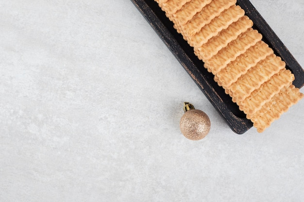 Koekjes en kerstbal op marmeren oppervlak