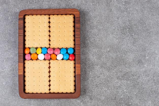 Koekjes en kleurrijk suikergoed op houten plaat