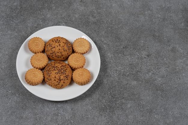 Koekjes en koekjes op de plaat op het marmeren oppervlak