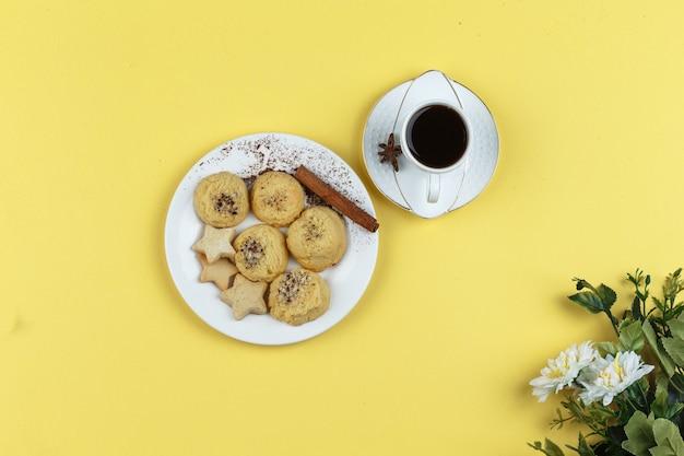 Koekjes en koffiekop op een gele achtergrond