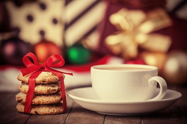 Koekjes en kopje koffie met kerstcadeaus op de achtergrond