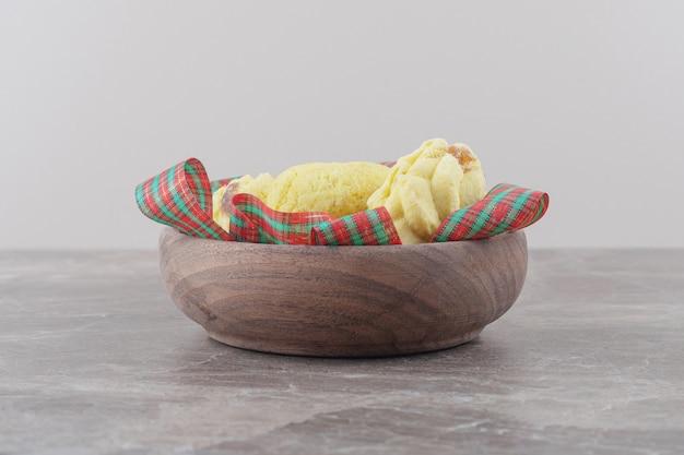 Koekjes en linten in een kleine kom op marmer