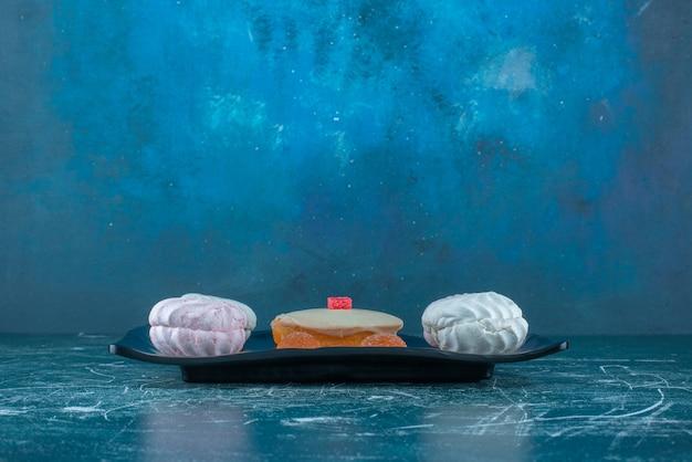 Koekjes en marmelades rond een witte chocolade bedekte cake op een schotel op blauwe achtergrond. hoge kwaliteit foto