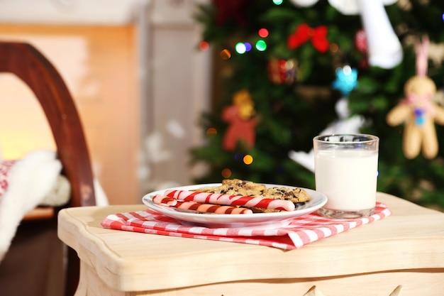 Koekjes en melk voor de kerstman op tafel, op een prachtig kerstinterieur