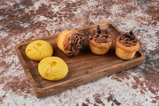 Koekjes en muffins op een houten bord.