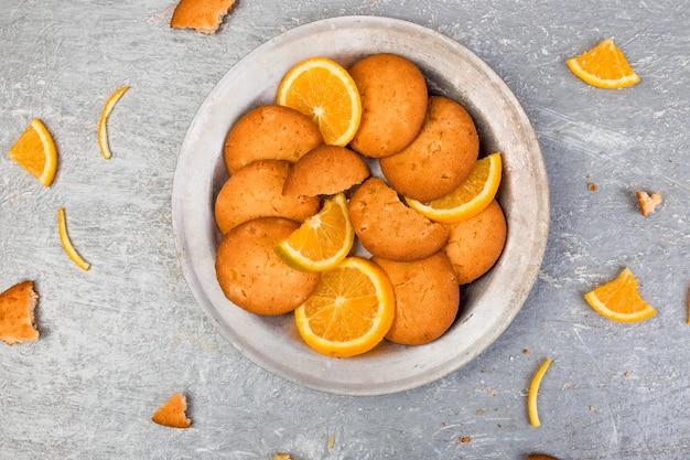 Koekjes en oranje citrusvruchten op metaalplaat op grijze achtergrond