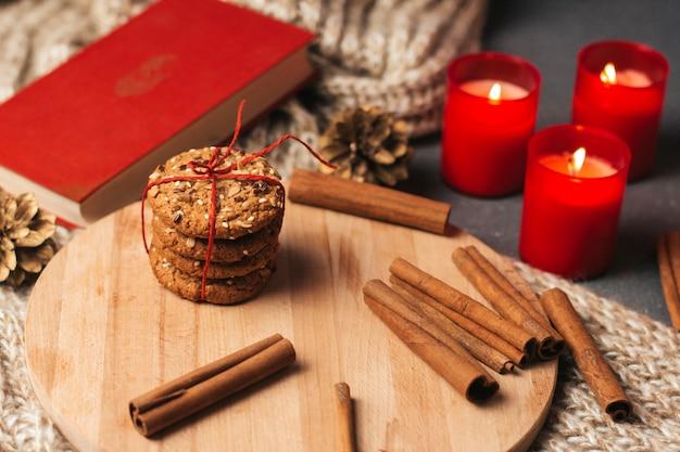 Koekjes en pijpjes kaneel op een houten bord.