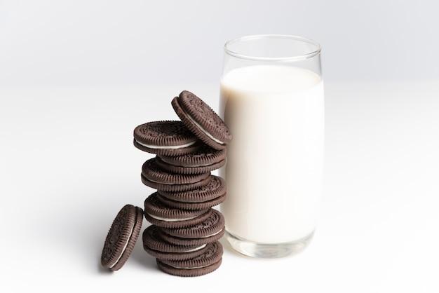 Koekjes en room van chocoladesmaak in stapel met glas verse melk op witte backgrou
