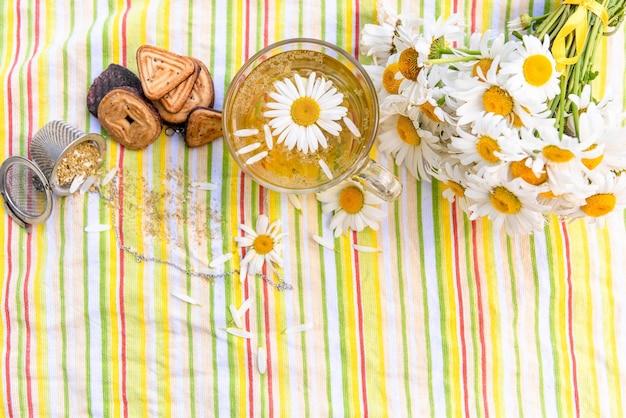 Koekjes en thee met toevoeging van kamilleblaadjes in de natuur.