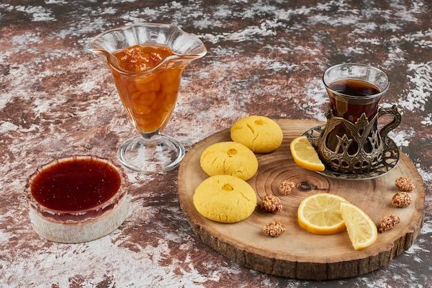 Koekjes en thee op een houten bord.