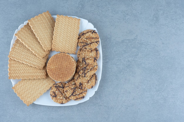 Koekjes en wafels op witte plaat. bovenaanzicht van verse koekjes.