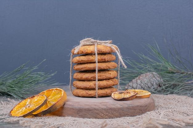 Koekjes gebonden met een draad op een houten bord met droge stukjes sinaasappel