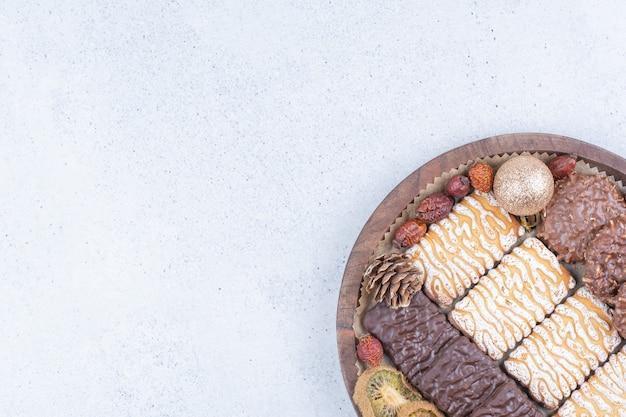 Koekjes, gedroogd fruit en kerstballen op een houten bord.