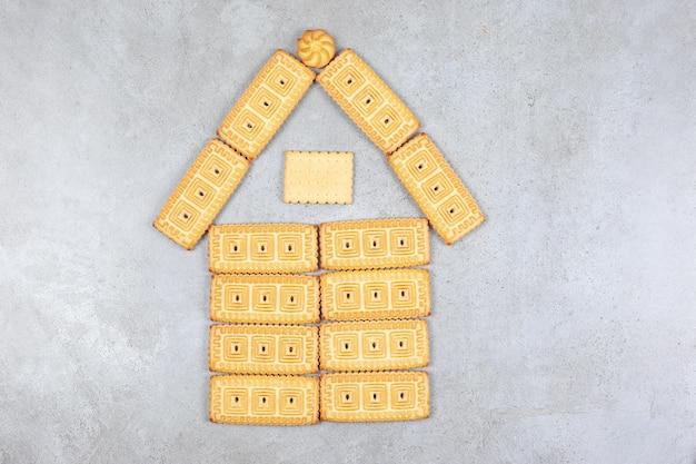 Koekjes gerangschikt in huis figuur op marmeren achtergrond.