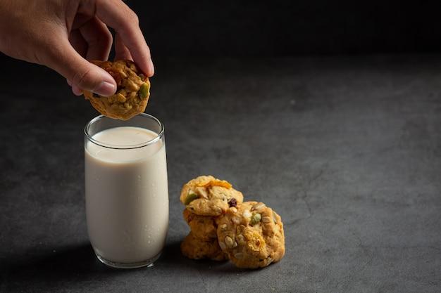 Koekjes geserveerd met een glas melk op een donkere vloer
