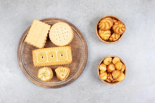 Koekjes gestapeld op een houten dienblad naast kommen koekjeschips op marmeren oppervlak
