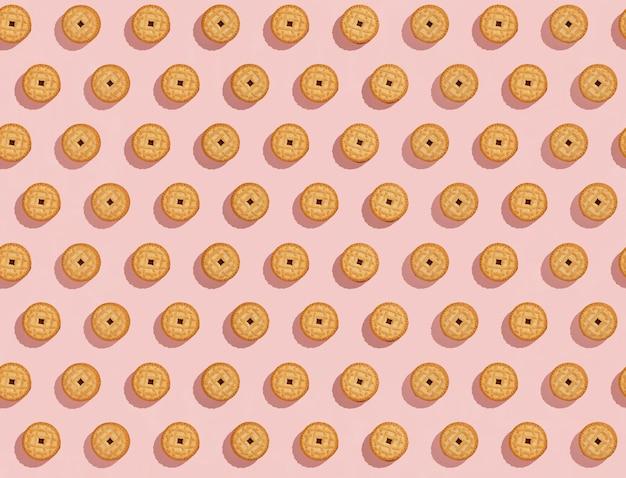 Koekjes gevuld met crème naadloos patroon op roze