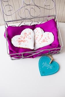 Koekjes in de vorm van een hart op een roze servet met thuis inscriptie