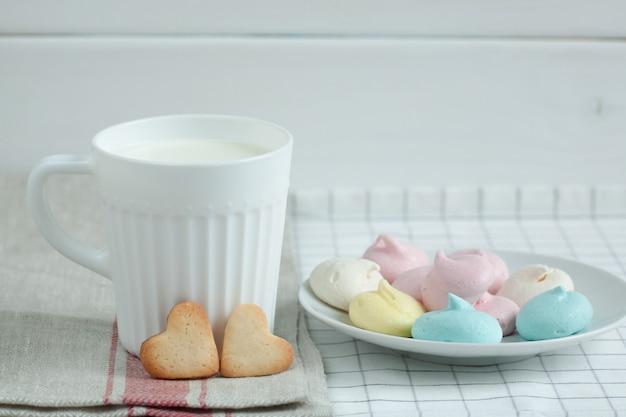 Koekjes in de vorm van harten en meringue melk.