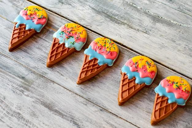 Koekjes in de vorm van ijs. kleurrijke koekjes op grijze achtergrond. zoete snacks voor kinderen. smaak van geluk.