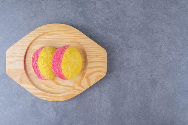 Koekjes in de vorm van perziken op een houten bord op marmeren tafel.