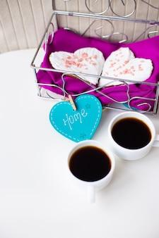 Koekjes in een hart en twee kopjes koffie op de tafel die naar huis zegt