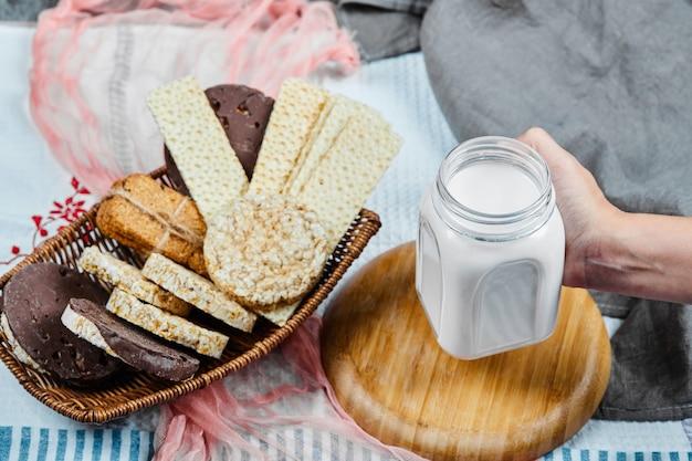 Koekjes in een mand en hand die een kruik melk op een tafelkleed houden.